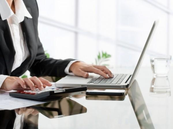 kobieta liczy na kalkulatorze i pisze na komputerze